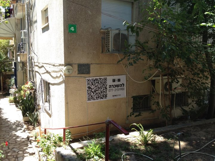 שלט על גבי נכס עם ברקוד סרוקאוטו המאפשר צפייה בנכס מבחוץ ללא תיאום